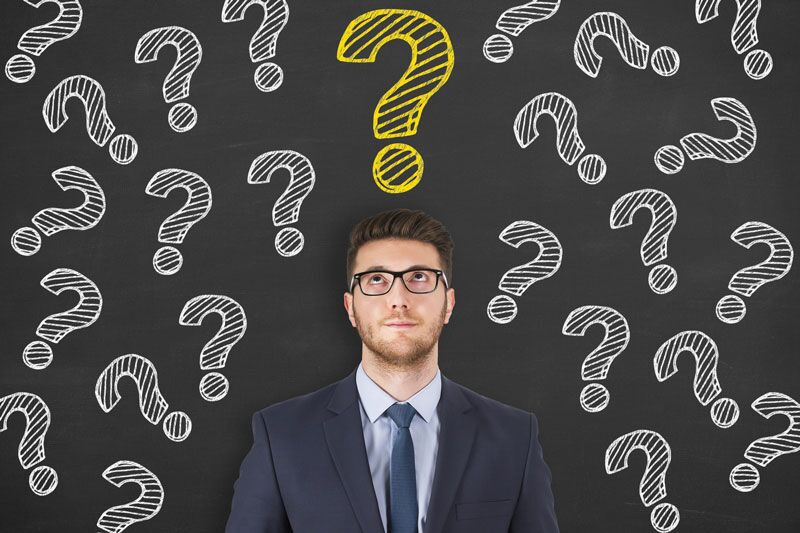 man standing in front of blackboard covered in questions marks