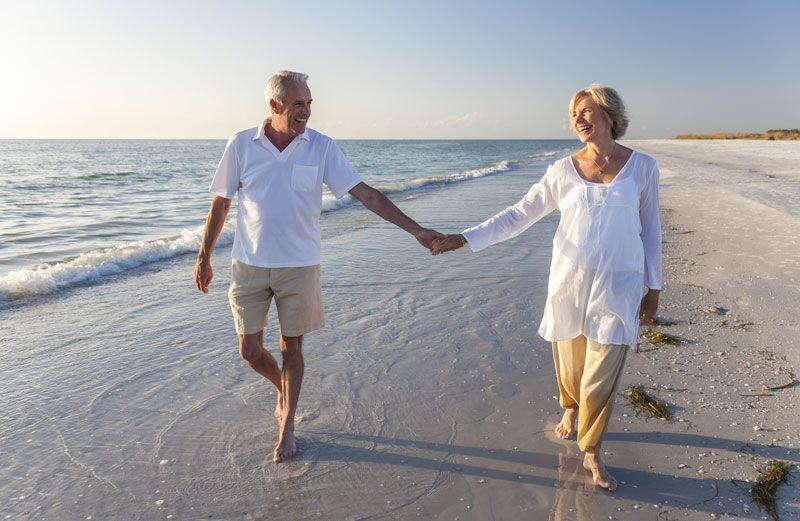 older couple waking on beach
