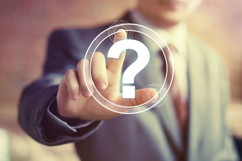 man in suit hitting question mark button